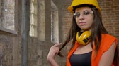lovable : Young pretty attractive women in helmet, earphones and glasses looking, pointing in camera, touching her long hair, smiling, female builder, brick building background