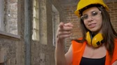 contramestre : Young charming attractive women in helmet, earphones and glasses looking, pointing in camera, smiling, female builder, brick building background