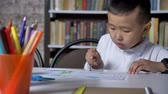 сконцентрировать : Young little asian boy painting on paper and sitting behind table, kid doing homework, book shelves background
