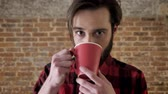 çekmek : Yound attractive man with beard is drinking tea, watching at camera, brick background Stok Video