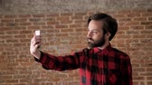çekmek : Young handsome man with beard make selfie on his smartphone, comunication concept, brick background
