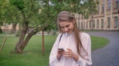 bites lip : Young beautiful girl types messages on her smartphone in summer, flirt conception, communication concept