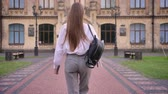 брюки : Young girl student is going to university in summer, studying concept, back view Стоковые видеозаписи