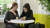 muslimah : Two young beautiful womans sitting in cafe, one of them muslim woman in hijab, looking at phone and laughing, happy