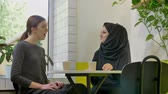 muslimah : Two young beautiful womans sitting in cafe and talking, one of them pretty muslim woman in hijab, smiling