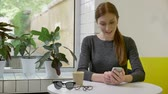 rabo de cavalo : Young charming woman with ponytail sitting in cafe and typing on phone, surprised and smiling Stock Footage