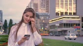 Young beautiful girl is typing message on her smartphone at sunset in city center in summer, communication concept