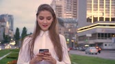 Young happy girl is typing message on her smartphone at sunset in city center in summer, communication concept