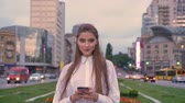Young happy girl is typing message on her smartphone at sunset in city center in summer, thinking concept, communication concept