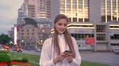 Young beautiful girl is typing message on her smartphone at sunset in city center in summer, thinking concept, communication concept