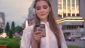 Young cute girl is watching on her smartphone at sunset in city center in summer, thinking concept, communication concept Wideo