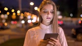 Young serious girl is reading message on her tablet in evening in summer, communication concept