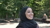 pakistan : Young happy muslim girl is walking in park in daytime in summer, smiling, watching around, religious concept