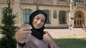 Young beautiful muslim girl in hijab is making selfie on her smartphone, showing like sign in daytime in summer, building on background, religiuos concept, communication concept