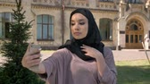 make photo : Young beautiful muslim girl in hijab is making selfie on her smartphone, showing like sign in daytime in summer, smiling, building on background, religiuos concept, communication concept