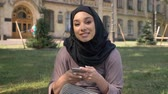 islamite : Young beautiful muslim girl in hijab is watching at smartphone in daytime in summer, watching at camera, smiling, building on background, religiuos concept, communication concept Stock Footage