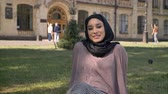 islamite : Young happy muslim girl in hijab is sitting on lawn in sun, watching at camera, builging on background, religious concept, relax concept