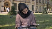 Young muslim girl in hijab is sitting on lawn and reading magazine, builging on background, religious concept, relax concept Wideo