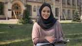 islamite : Young muslim girl in hijab is sitting on lawn and reading magazine, watching at camera, smiling, builging on background, religious concept, relax concept Stock Footage