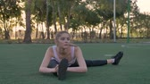 Young pretty woman stretching on soccer field in park, morning work-out, fitness model exercising