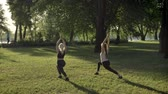 Two young womans doing yoga in park near river during morning, lens flare and beautiful view background Wideo