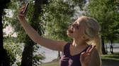 Young pretty blonde woman taking selfie with her phone, showing tongue and smiling in park near river
