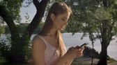 Young pretty woman typing on her phone, looking in camera in park near river and smiling, beautiful view Wideo