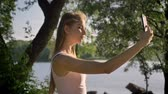 energy body : Young pretty woman with long hair taking selfie with her phone and smiling, park near river background, beautiful view