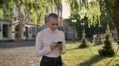 young extraordinary bold girl is walking through park in daylight, in summer, typing message on smartphone, watching at camera communication concept, building on background Wideo