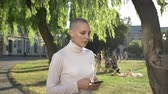 young extraordinary bold girl is walking through park in daylight, in summer, typing message on smartphone, communication concept, thinking concept