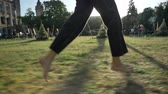 Legs of women run on grass in park in daytime in summer, healthy lifestyle, blured background Wideo
