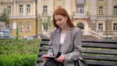 satisfeito : Young beautiful ginger woman in jacket sitting on bench and holding tablet, city street background Stock Footage