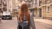 Young woman with long ginger hair walking on city street and inviting somebody to go with her, urban street background, back view