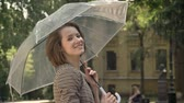 varredura : Young attractive girl is walking in park with umbrella in daytime, in summer, smiling, watching at camera