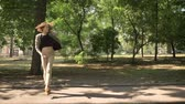 step by step : Young beautiful girl is dancing on path in park in daytime, in summer, movement concept, side view, dolly shot