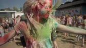 discotheque : Young happy girl in colourful powder is jumping and shaking head on holi festival in daytime in summer, color concept