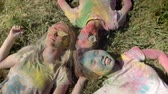 фест : Three young happy multi-ethnic girlfriends are laying on grass on holi festival in daytime in summer, friendship concept, holiday concept