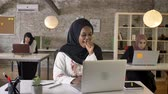 pakisztán : Young black muslim women in hijab working on laptop and yawning, sleepy, three beautiful muslim womens sitting in modern office