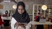 middle eastern ethnicity : Young black muslim women in hijab using tablet, looking in camera, smiling, islamic business womens typing on laptop in modern office Stock Footage