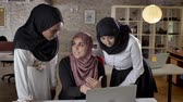 islamite : Young muslim womens in hijab discussing project and pointing in laptop, talking about business plan in modern office