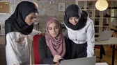 islamite : Team of young muslim womens in hijab discussing business-plan and pointing in laptop, talking about project in modern office