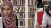 islam : Three young muslim womens in hijab studying in library, reading and writing, shelves with books background, islamic students