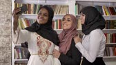 academia : Three young charming muslim womens in hijab taking selfie in library, friends taking photos of themself, smiling and happy Stock Footage