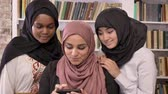 islamite : Three young beautiful muslim womens in hijab taking selfie in library and looking at phone after, smiling