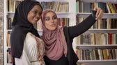 islamite : Young african muslim women in hijab with white friend taking selfie in library, then looking at phone, smiling and happy, islamic students