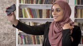 muayene : Portrait of young muslim pretty women in hijab taking selfie then looking at phone and watching photos in library, smiling