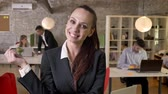 iş arkadaşı : Young cute businesswoman is watching at camera in office, smiling, her colleagues are networking with technologies, working concept, business concept, blurred background