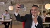 make photo : Young businessman is making selfie on smartphone in office, fools around, his colleagues are networking with technologies, working concept, business concept, communication concept