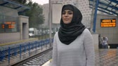 sonhador : Young muslim woman in hijab is waiting for train n railway station, raining, religion concept, urban concept. weather concept