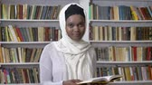 islamite : Young african muslim girl in hijab is holding book, watching at camera, religioun concept, booksheves on background